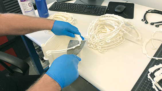 Volunteers cut 3D-printed components for protective face shields.
