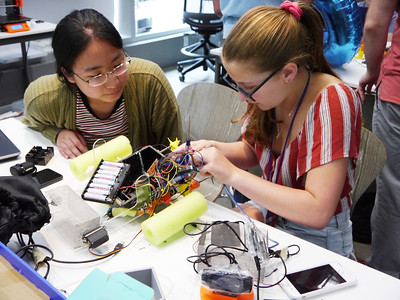 Two students work on assembling an electronics circuit for a remote control vehicle.