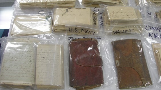 Photo of 19th century letters and wallets in labeled plastic bags