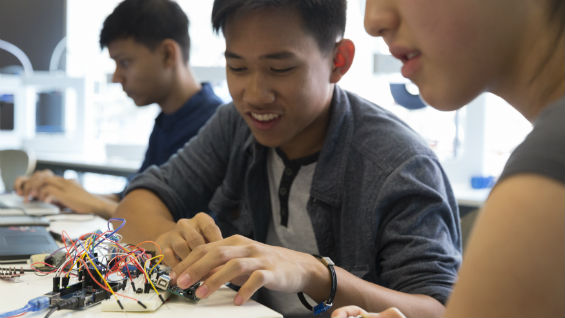 Two students work on assembling an electronics circuit on a bread board.