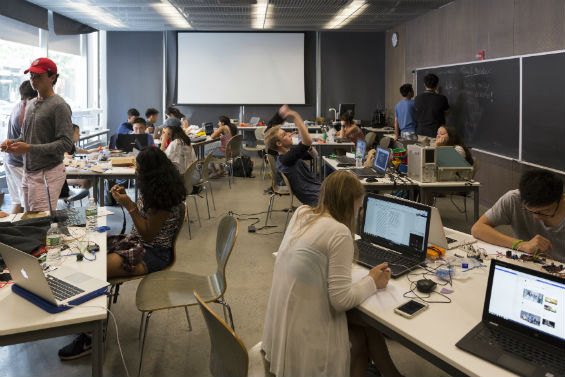 A room of students have computers out to work on programming microcontrollers.