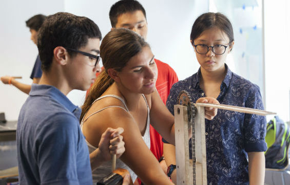 Summer STEM students test a gear for an elevator in the Rube Goldberg machine.