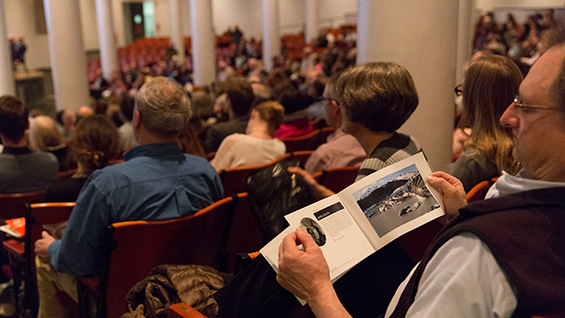 An audience member views the program that includes many striking photos