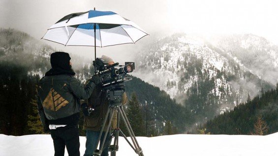 Photo by Matt Anderson. Michael Gerner holds an umbrella over cinematographer David Black to get a shot of the mountains in Mont