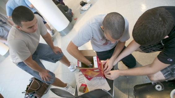 Anthony Traina, Frank Longueira and Joseph Viola manipulate a family-sized Cheez-It box