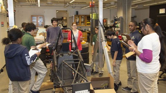 MELS students listen as mechanical engineering senior Kim Meehan explains the materials that make an automobile
