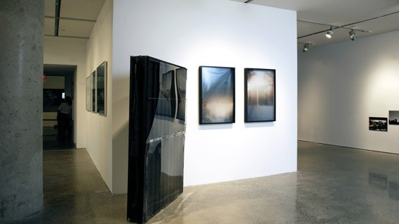 Installation view of Oscar Tuazon's Black Slab, 2008 (center right) and Afognak (triptych), 2008 (center left)
