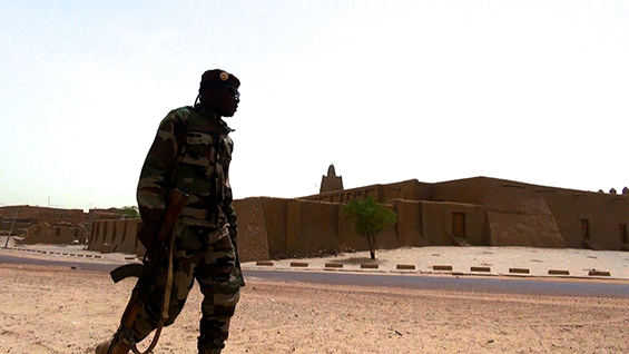 A soldier patrols in front of Djinguereber Mosque, Timbuktu. Image by Francois Rihouay from 'The Destruction of Memory'. © Vast Productions USA 2016