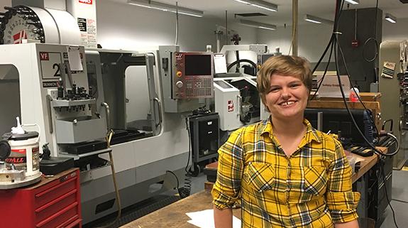 Jenna Scott in front of Cooper's CNC milling machine
