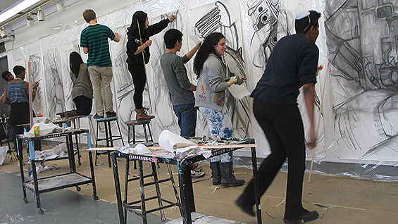 Current members of the Student Portfolio class create large-scale charcoal drawings