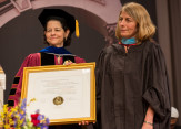 Rachel Warren, chair of the Board of Trustees, awarded an honorary degree to Sacha Pfeiffer.