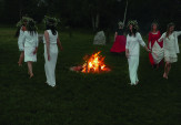 Women honor the fire by dancing with crowns of field flowers on their heads