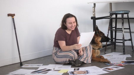 Oaklee Thiele and her medical alert service dog, Coco, sitting on the floor of the Cooper studios as she organizes the first issue of To Be Young (And Disabled)